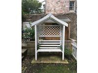 White garden bench with trellising