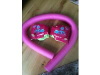 Pink swim noodle and speedo arm bands
