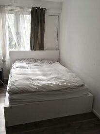 King size bed with white bed frame and storage drawers