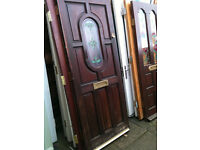 Exterior hardwood door with oval patterned glass panel