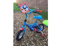 Thomas bike with stabilisers and helmet