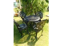 four black heavy garden patio chairs and matching table