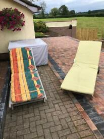 2 wooden sun loungers with cushions