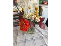Artificial flowers in glass vase & red candle holders