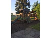 Large wooden play area with slide, swings, ramps, climbing walls
