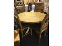 Round oak table and four oak chairs—unused—