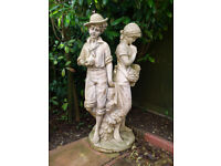 A LARGE STATUE of a BOY & GIRL