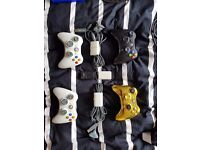 4 xbox 360 controllers with batteries and cables.