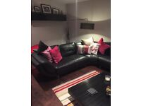 Black leather corner sofa with footstool