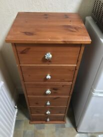 Tall, slim chest of drawers with decorative handles