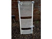 Clean tidy, fully functional white curved towel radiator with all fixtures and fittings.