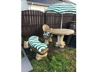 Concrete table furniture bench and stools with cushions and parasol