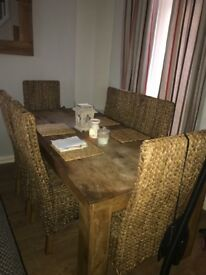 Solid oak table and 6 wicker chairs Top of table slightly marked but can be sanded and waxed