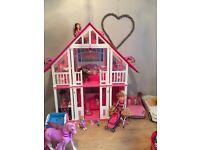 Barbie house and lots of extras including barbies, cars etc...