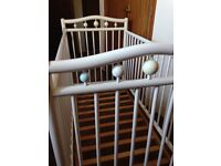 Baby cot in white. Has wheels and different heights complete with bedding etc.
