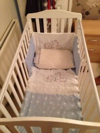 White baby cot, bedding and mobile