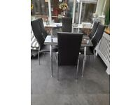 Black glass ding table with silver legs and 6 chairs I