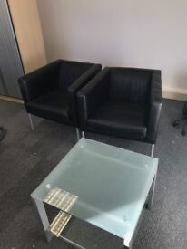 Two black leather look office tub chairs and glass table