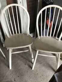 Two wooden chairs in need of a repaint