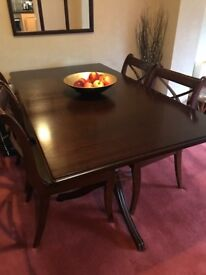Rich dark wood dining table with matching chairs