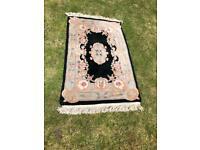 Used patterned black rug