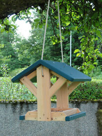 Hand crafted wooden bird feeders for hanging in a tree.