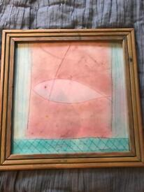 Delightful, square pink pastel picture of a fish in a wooden frame.