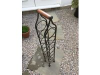 Cast iron wine rack with dark wooden handle