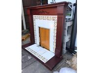 Reclaimed mahogany colour fire surround and ornate lily tiled back plate and hearth
