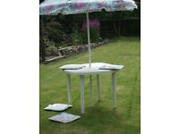White garden table with parasol and seat covers