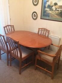 Wooden dining room table with five chairs