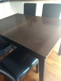 Dark wood dining table and four faux leather chairs