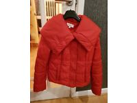 Red jacket for sale. Padded with large collar. 2 side pockets. Button up front.