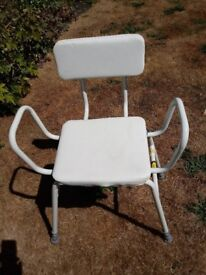 Perching stool with padded seat and backrest.