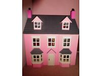 Beautiful pink dolls house, fully decorated and with people and furniture.