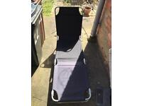 Two black fold out sun loungers