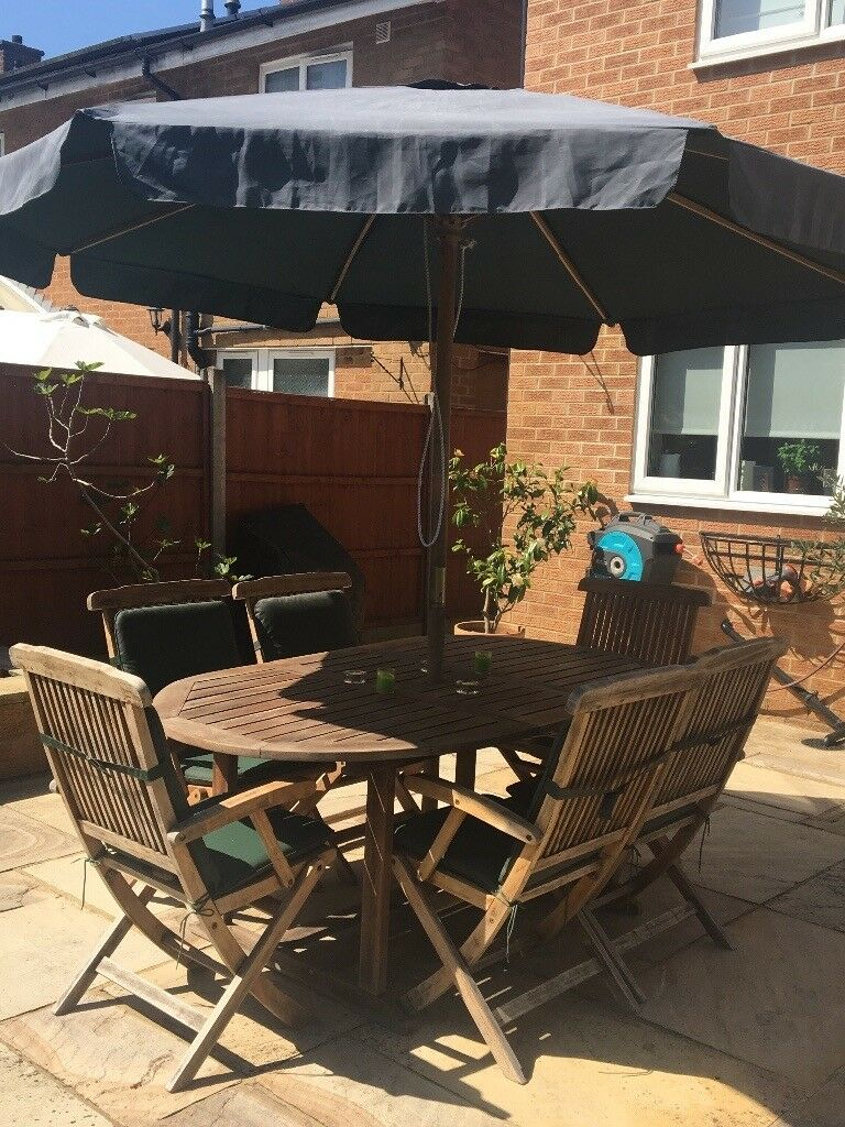Outdoor hardwood table 6 chairs with seat covers and an umbrella