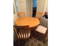 Circular, extendable, solid wood dining table and six matching chairs
