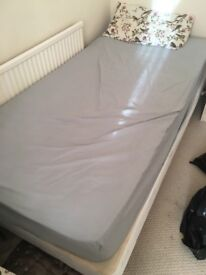 Single bed with mattress and wooden legs