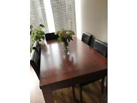 Dark brown wooden dining table with 5 chairs.