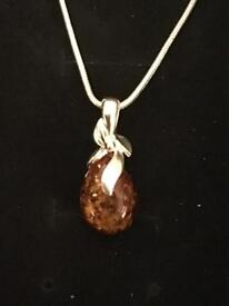 Ladies sterling silver pendant and chain with a genuine Baltic amber stone