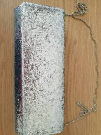 Glittery clutch purse, never used. Has a detachable chain.