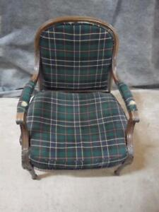 Chair with detailed wood frame, tartan pattern fabric back, seat and arm rests.