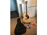 As new condition Yamaha F370 Acoustic Guitar. Includes stand, DVD and Book