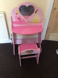 A dressing up desk with a chair for a girl