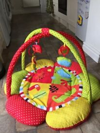 Red baby gym playmat with soft pad and hanging toys in excellent condition