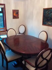 Beautiful dining table with six high back upholstered chairs.