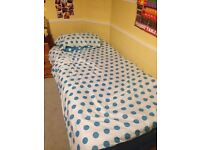 Single bed with mattress and bedding