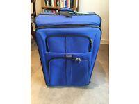 Large blue Delsey wheeled suitcase