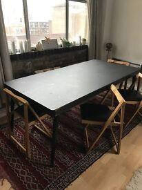 large modern black dining table with six folding chairs
